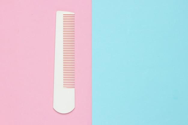 Pente de plástico branco em pastel rosa azul. cuidados com os cabelos, conceito de beleza. vista do topo Foto Premium