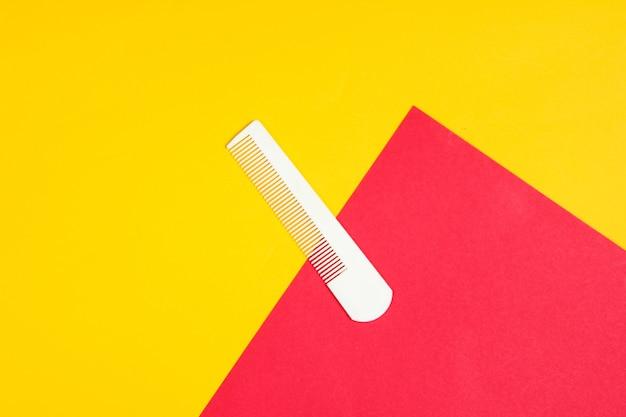 Pente de plástico branco sobre um vermelho-amarelo. cuidados com os cabelos, conceito de beleza. vista do topo Foto Premium