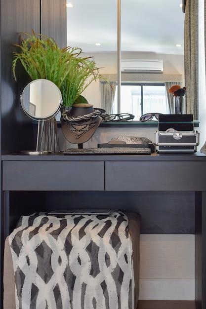Penteadeira de madeira preta com cadeira marrom e acessórios em casa Foto Premium