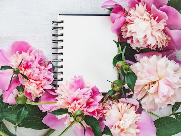 Peônias brilhantes, página de bloco de notas em branco sobre uma mesa de madeira Foto Premium