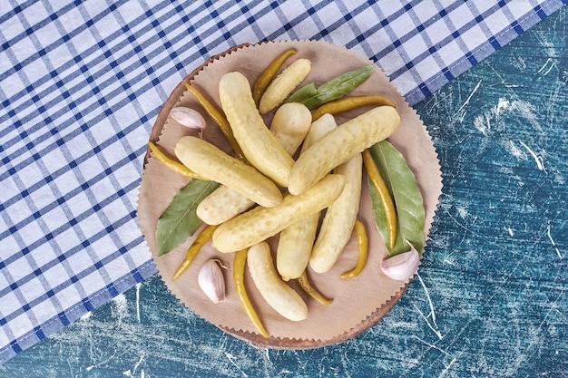 Pepinos em conserva, alho, pimentão e folhas na placa de madeira com toalha de mesa. Foto gratuita