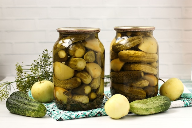 Pepinos em vinagre com maçãs em frascos são dispostos em um fundo branco Foto Premium