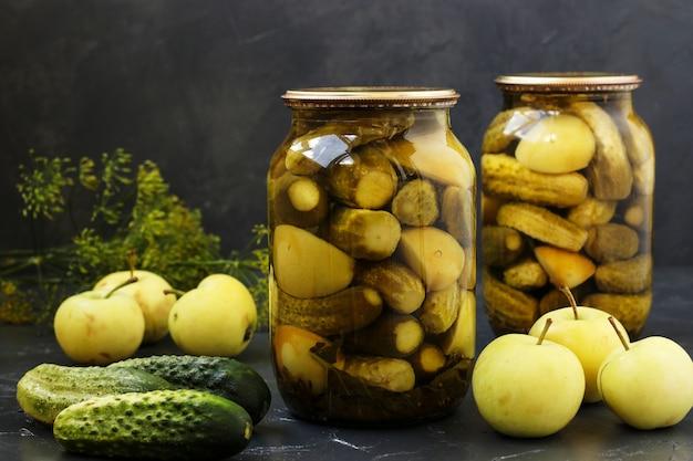 Pepinos em vinagre com maçãs em frascos são organizados Foto Premium