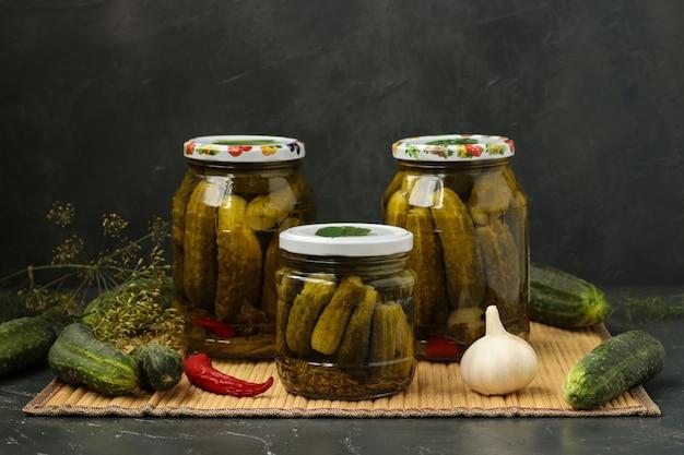 Pepinos em vinagre em vasos estão localizados sobre uma mesa, sobre um fundo escuro. Foto Premium