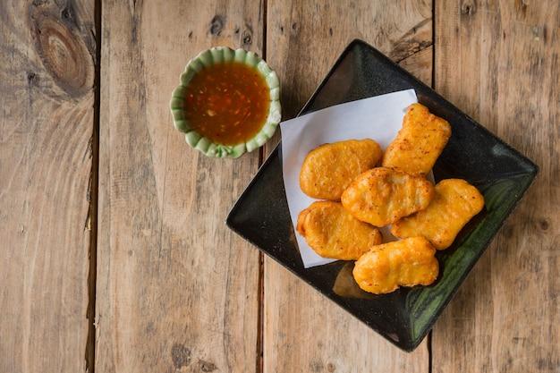 Pepita de galinha com o aperitivo do alimento do molho picante pronto para comer na tabela de madeira. Foto Premium