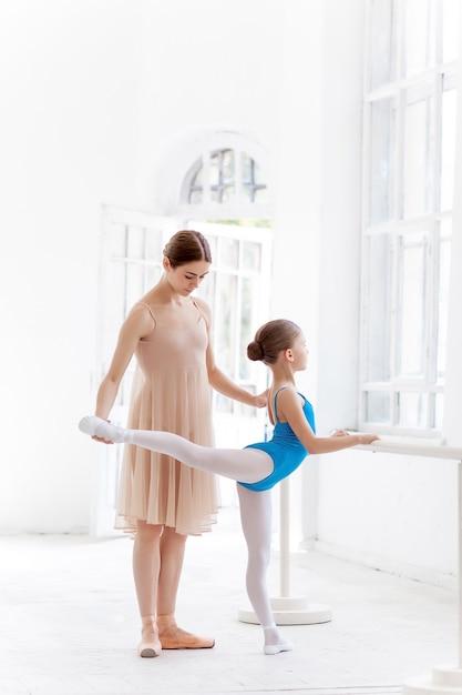 Pequena bailarina posando com professor pessoal no estúdio de dança Foto gratuita