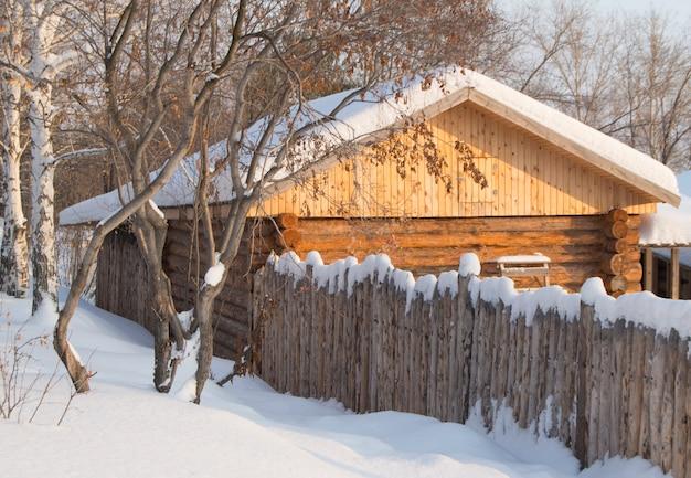 Pequena cabana de madeira em uma floresta de neve Foto Premium