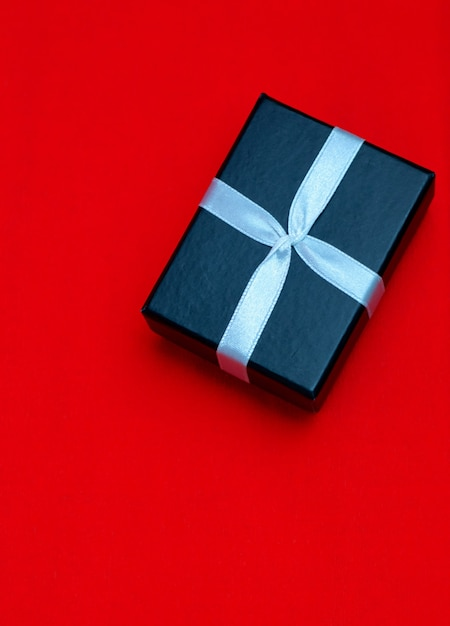 Pequena caixa de presente retangular preta sobre fundo vermelho Foto Premium