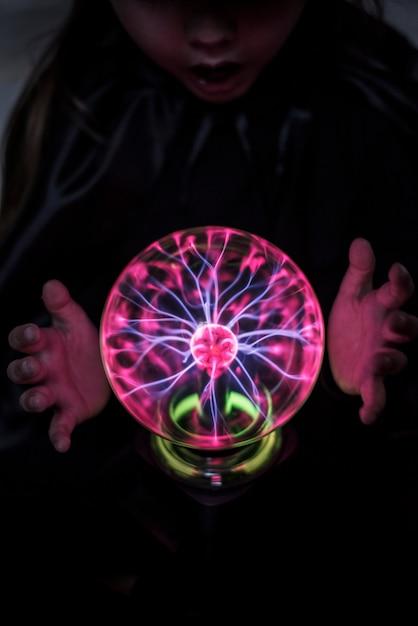 Pequena cartomante com uma bola de plasma Foto gratuita