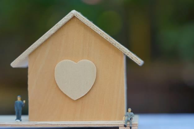 Pequena casa de madeira com figuras perto Foto Premium