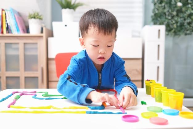 Pequena criança asiática se divertindo jogando argila de modelagem colorida / massinha em casa, criança em casa, jardim de infância fechada Foto Premium