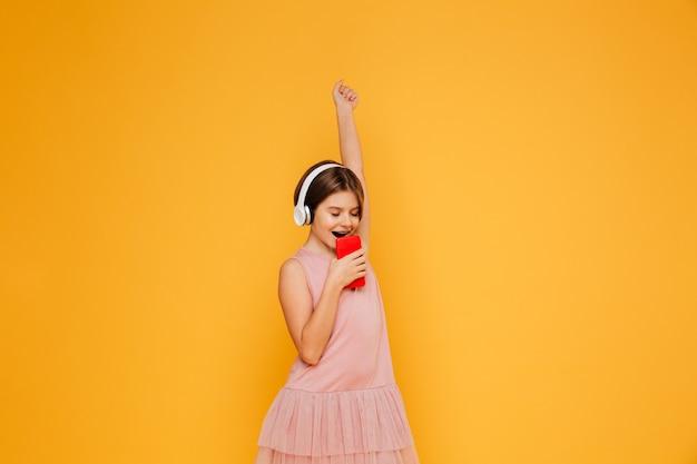 Pequena dama em fones de ouvido cantando no smartphone isolado Foto gratuita