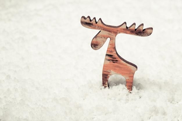 Pequena figura de madeira de veado na neve, cartão de feliz ano novo. Foto Premium
