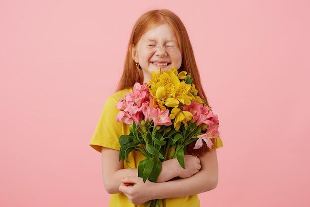 Pequena garota ruiva de sardas com duas caudas, com os olhos fechados amplamente sorrindo e parece fofa, segura o buquê, usa uma camiseta amarela, fica sobre fundo rosa. Foto gratuita