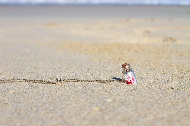 Pequena garrafa na praia de areia branca fundo do mar azul-turquesa Foto Premium
