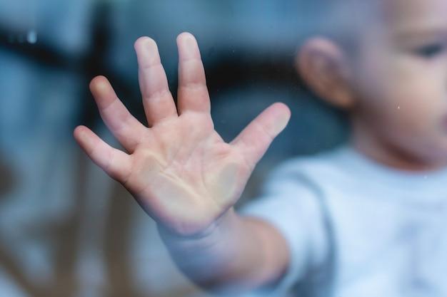 Pequena mão da criança é pressionada contra o vidro da janela com reflexão. solidão das crianças. orfanato e órfãos Foto Premium
