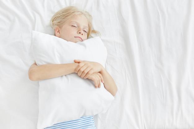 Pequena menina adorável com cabelo loiro, rosto sardento, fechando os olhos, abraçando o travesseiro branco, dormindo agradavelmente em roupas de cama branca. criança tendo sonhos agradáveis de manhã descansando em casa Foto gratuita