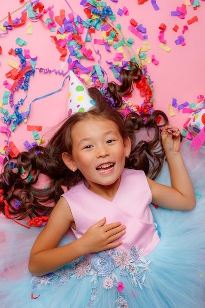 Pequena menina asiática, chapéu de aniversário, sorriso, presente, confete, deitada de costas, vista superior, Foto Premium