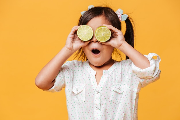 Pequena menina bonito, cobrindo os olhos com limão. Foto gratuita
