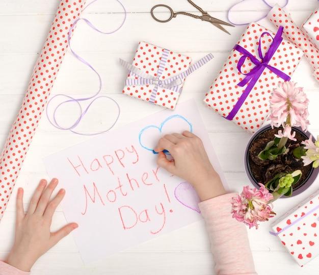 Pequena menina desenhando um cartão de felicitações Foto Premium
