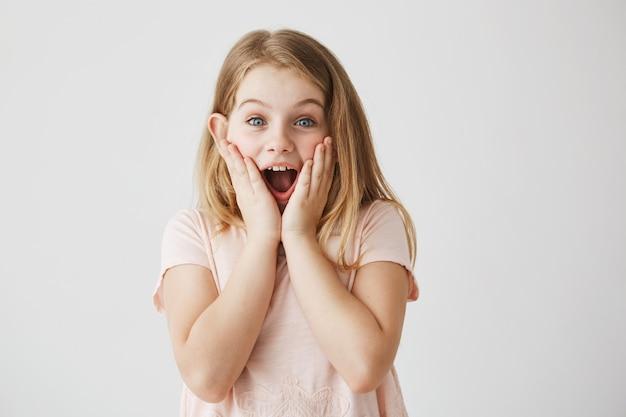 Pequena menina loira de olhos azuis, segurando o rosto com as mãos e boca aberta, expressando emoção. garoto ficando feliz depois de receber o presente de aniversário da mãe. Foto gratuita