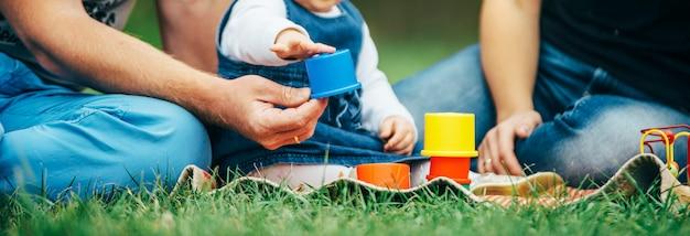 Pequena menina vestida de jeans brincando com os pais Foto Premium