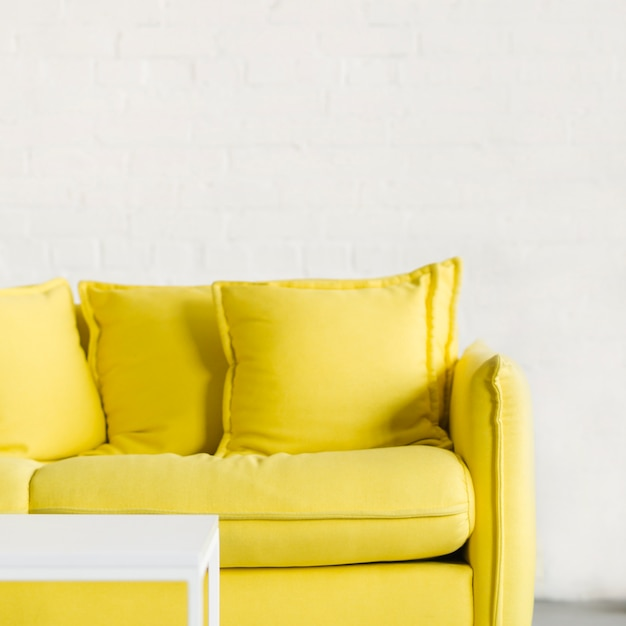 Pequena mesa branca na frente do sofá amarelo contra a parede de tijolos brancos Foto gratuita