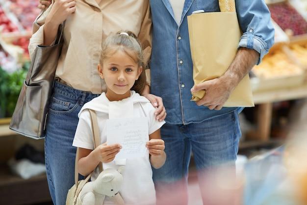 Pequena mulher com os pais no supermercado Foto Premium