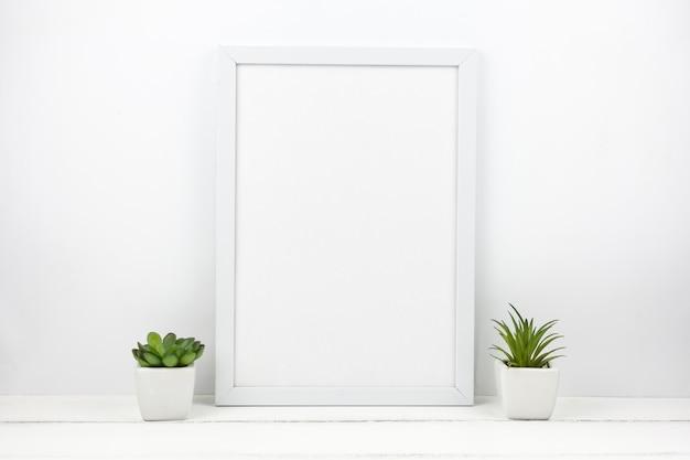 Pequena planta suculenta e moldura vazia em casa Foto gratuita