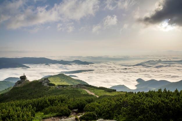 Pequena silhueta de turista com os braços erguidos na formação rochosa no vale da montanha cheia de nuvens brancas inchadas e neblina e coberta com encostas de montanhas sempre verdes da floresta sob o céu claro Foto Premium