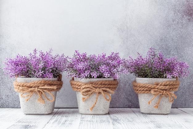 Pequenas flores roxas em vasos de cerâmica cinza em fundo de pedra estilo rústico Foto Premium