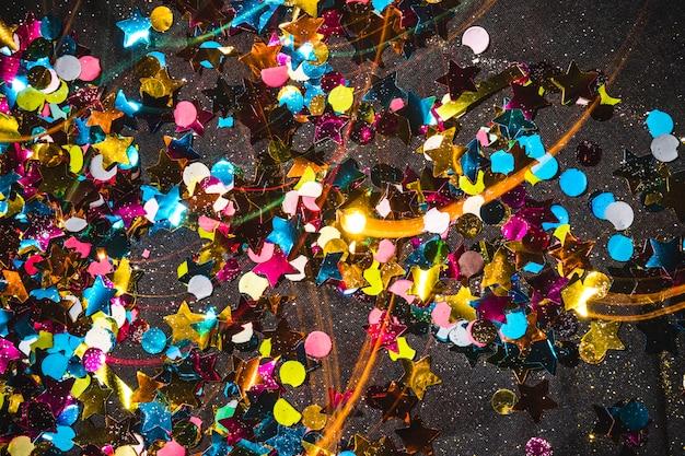 Pequenas lantejoulas espalhadas na mesa escura Foto gratuita