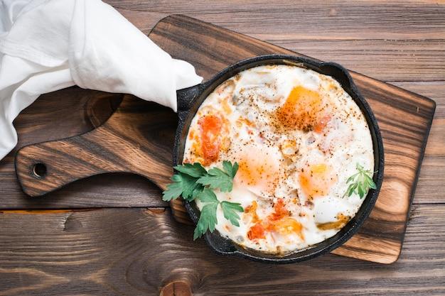 Pequeno-almoço caseiro de shakshuka ovos fritos com tomate e ervas em uma panela sobre uma mesa de madeira Foto Premium