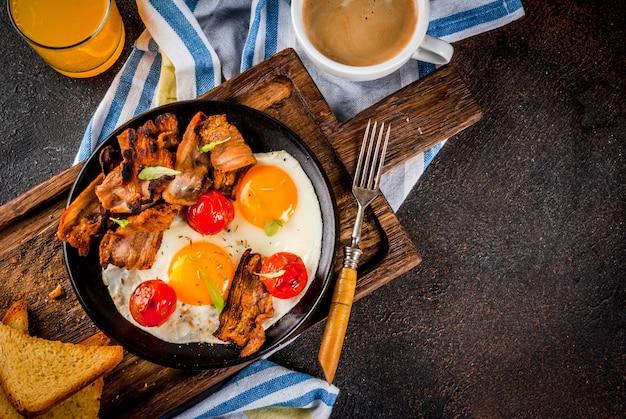 Pequeno-almoço inglês americano caseiro tradicional, ovos fritos, torradas, bacon, com caneca de café e suco de laranja Foto Premium