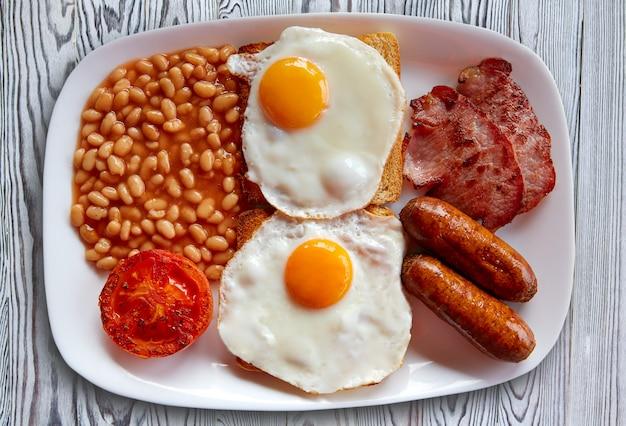 Pequeno-almoço inglês com dois ovos, feijão de salsicha Foto Premium