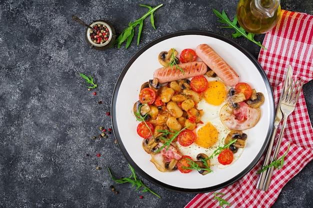 Pequeno-almoço inglês - ovo frito, feijão, tomate, cogumelos, bacon e salsicha. comida saborosa. Foto Premium