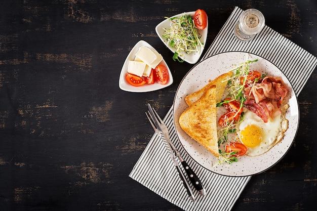 Pequeno-almoço inglês - torrada, ovo, bacon e tomate e salada microgreens. vista do topo. lay plana Foto Premium