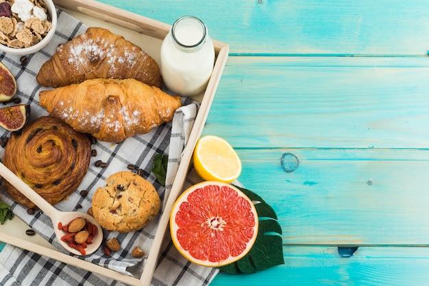 Pequeno-almoço saudável com croissant; cookies com suporte; leite; muesli; e frutas cítricas na bandeja de madeira Foto gratuita