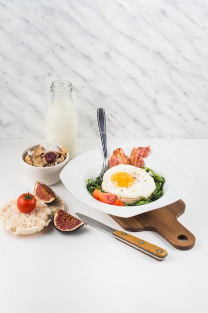 Pequeno-almoço saudável com garrafa de leite; flocos de milho; biscoito de figo e arroz contra o pano de fundo texturizado mármore Foto gratuita