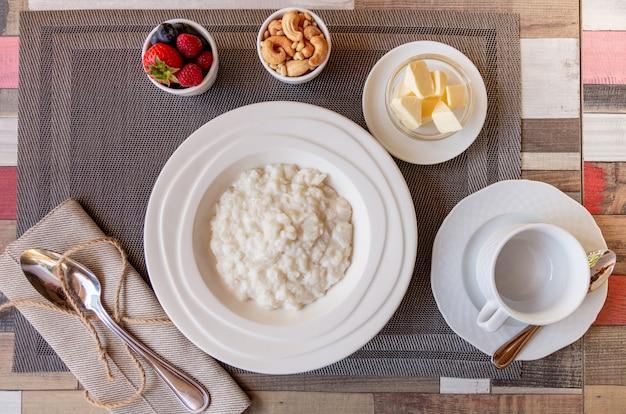 Pequeno-almoço saudável com tigela de mingau de arroz com frutas e nozes em cima da mesa Foto Premium