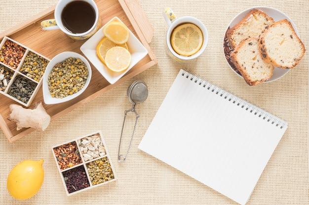 Pequeno-almoço saudável com variedade de ervas; limão; filtro; pão; bloco de notas em espiral de gengibre e em branco Foto gratuita