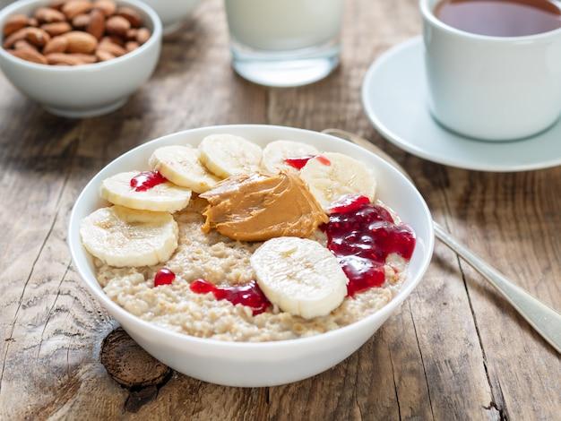 Pequeno-almoço saudável de manhã - aveia com fatias de banana, geléia de framboesa e manteiga de amendoim. Foto Premium