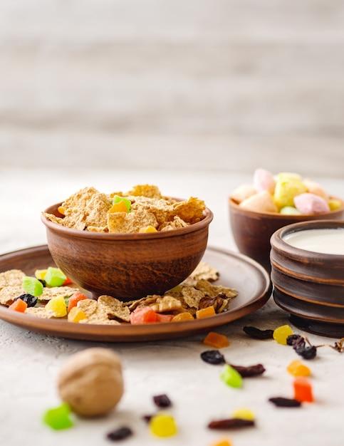 Pequeno-almoço saudável (flocos de trigo, nozes, frutas cristalizadas, passas, leite) Foto Premium