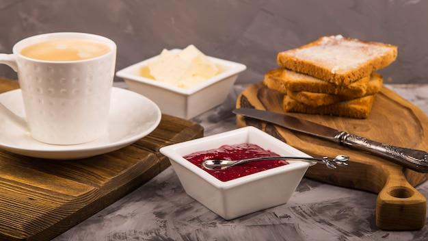 Pequeno-almoço simples de produtos tradicionais - torrada com manteiga e geléia de framboesa Foto Premium