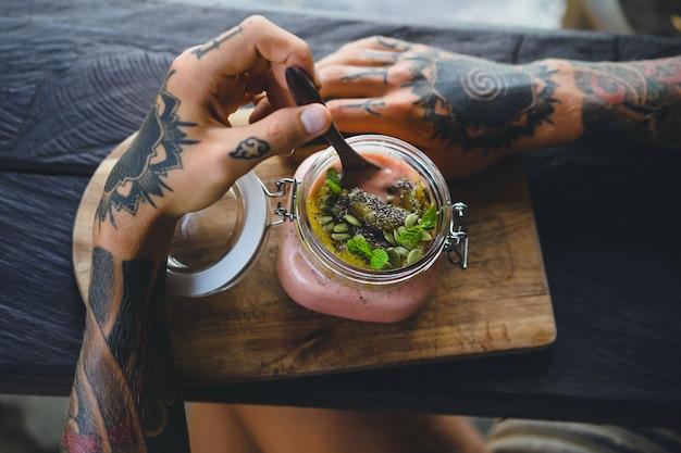 Pequeno-almoço útil. um belo café da manhã, as mãos dos homens em tatuagens. Foto gratuita