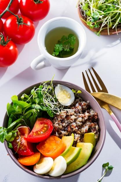 Pequeno-almoço vegetariano com quinoa, ovos, microgreen e legumes, chá verde com hortelã em uma mesa branca, plana leigos Foto Premium