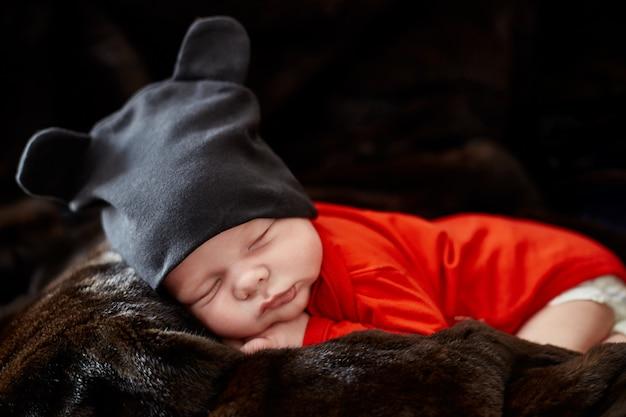 Pequeno bebê recém-nascido está deitado no sofá. primeiros dias Foto Premium