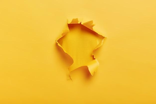 Pequeno buraco de papel com lados rasgados em um espaço amarelo para seu texto Foto gratuita