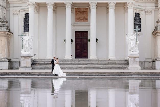 Pequeno casal de noivos está andando perto da enorme catedral com colunas brancas e reflexo na água Foto gratuita