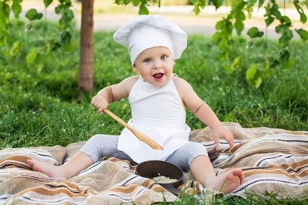Pequeno chef cozinha e come macarrão em um piquenique ao ar livre Foto Premium